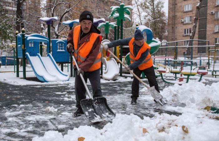 Дворники убирают снег на детской площадке