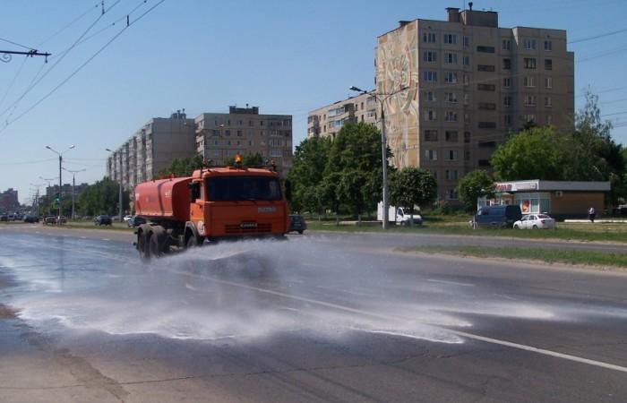 Машина поливает дорогу водой