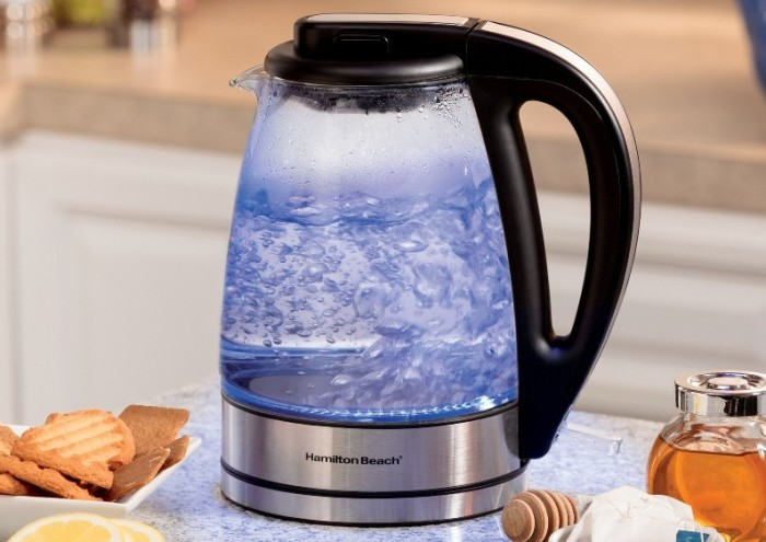 Современный стеклянный чайник кипятит воду