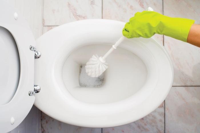 Чистка унитаза во время уборки в доме