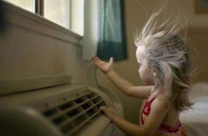 Девочка рассматривает домашний кондиционер