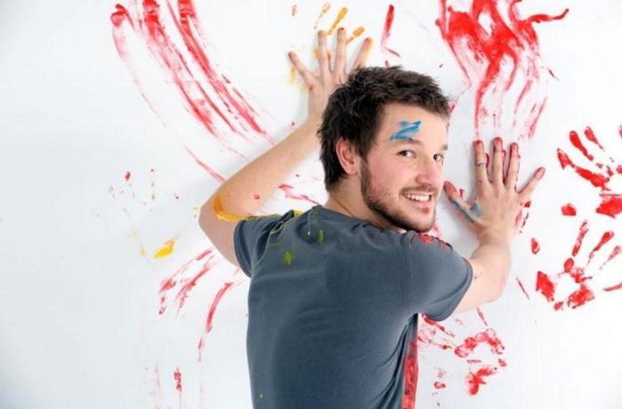 Мужчина рисует красками как может