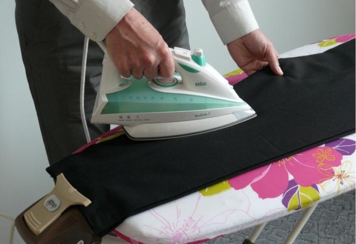 Мужчина гладит свои брюки
