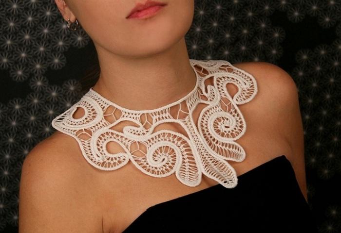 Белое вязаное украшение на шее девушки